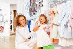 La petite fille avec sa mère choisissent la robe droite Photographie stock libre de droits