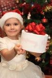 La petite fille avec un sapin proche actuel Photographie stock libre de droits