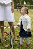 La petite fille avec un tricycle Image libre de droits