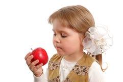 La petite fille avec une pomme rouge dans une main Photo stock