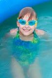 La petite fille ayant le bon temps dans la piscine Image libre de droits