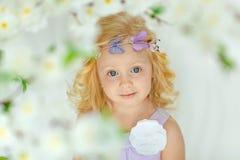 La petite fille blonde avec du charme sourit contre les portes blanches dans la lumière s Image libre de droits