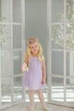 La petite fille blonde avec du charme sourit contre les portes blanches dans la lumière s Images libres de droits