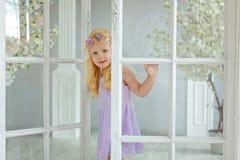La petite fille blonde avec du charme sourit contre les portes blanches dans la lumière s Photographie stock