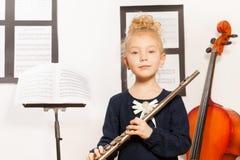 La petite fille blonde avec la cannelure se tient près du violoncelle Image stock