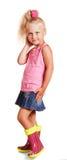 La petite fille blonde est dans le chemisier, jupe, bottes en caoutchouc photo stock