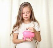 La petite fille blonde met la pièce de monnaie dans le moneybox porcin Image stock