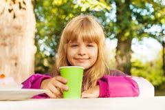 La petite fille blonde mignonne avec la tasse verte s'assied à la table Photos stock