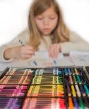 La petite fille blonde mignonne dessine par les crayons colorés, boîte de crayons sur le premier plan Photo stock