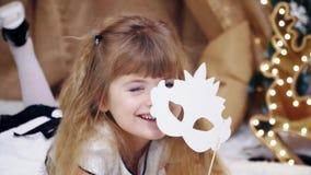 La petite fille blonde mignonne heureuse est se trouvante et posante avec un masque clips vidéos