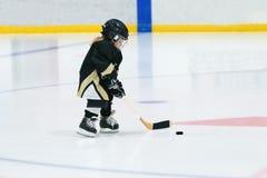 La petite fille blonde mignonne joue à l'hockey dans le plein équipement sur le stade Photographie stock