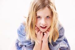 La petite fille blonde mignonne se penche sur ses mains tout en regardant dans l'appareil-photo photographie stock