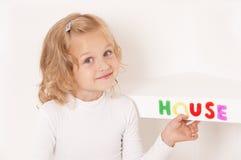 La petite fille blonde a rectifié dans le blanc Photographie stock libre de droits
