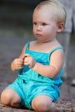 La petite fille blonde s'accroupit au sol par coucher du soleil Photo stock