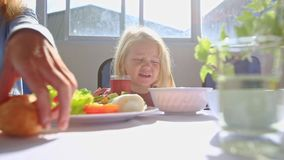La petite fille blonde s'assied aux boissons Juice Near Mother Eating Breakfast de Tableau clips vidéos