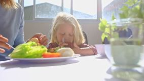La petite fille blonde s'assied aux boissons Juice Near Mother Eating Breakfast de Tableau banque de vidéos
