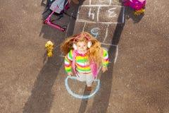 La petite fille blonde saute sur le jeu de marelle Photographie stock libre de droits