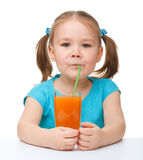 La petite fille boit du jus d'orange Photo stock