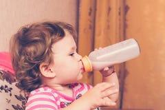 La petite fille boit du lait d'une bouteille photo stock