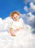 La petite fille bouclée avec les ailes féeriques se trouve sur un nuage Photographie stock