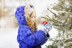 La petite fille bouclée décore l'arbre de Noël Photos libres de droits