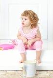 La petite fille bouclée dans une robe rose s'assied avec un regard et une montre réfléchis dans la distance, sur un porche blanc Images stock