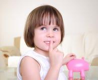 La petite fille cache son argent Images stock