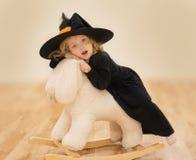 La petite fille caucasienne adorable s'assied sur le jouet pelucheux de lapin Elle est dans la robe noire et le grand chapeau noi Photos stock