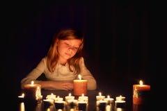 La petite fille caucasienne blonde regarde sur les bougies dans l'obscurité Photographie stock libre de droits
