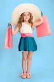 La petite fille caucasienne mignonne de brune dans la robe tenant des paniers Photo libre de droits