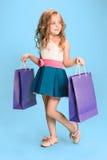 La petite fille caucasienne mignonne de brune dans la robe tenant des paniers Photos libres de droits