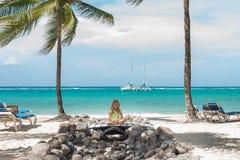La petite fille caucasienne s'assied sur la plage Le ciel bleu, les paumes et l'océan sont comme fond Photographie stock libre de droits