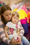 La petite fille choisit des espadrilles de chaussures dans la boutique pour des enfants Photo stock