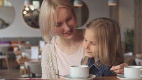 La petite fille chuchote dans son oreille du ` s de mère au café clips vidéos
