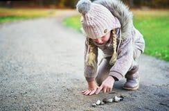 La petite fille compte des pierres sur une route Photo libre de droits