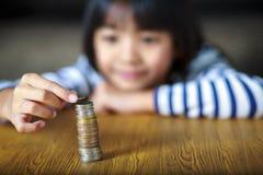La petite fille compte ses pièces de monnaie sur une table images libres de droits