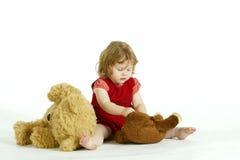 La petite fille concentrée jouant avec la peluche à photos stock