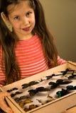 La petite fille contrôle la collection d'entomologie de papillons tropicaux images stock