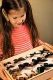 La petite fille contrôle la collection d'entomologie de papillons tropicaux photo stock