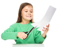 La petite fille coupe le papier utilisant des ciseaux Photo libre de droits