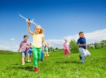 La petite fille court avec des enfants et tient le jouet d'avion Images stock