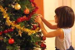 La petite fille décore l'arbre de Noël image stock