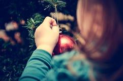 La petite fille décore l'arbre de Noël dans le rétro effet de filtre Image stock