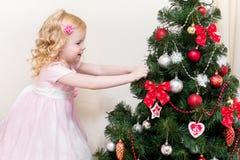 La petite fille décore un arbre de Noël Image stock