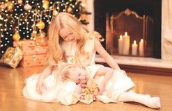 La petite fille d'enfant donne un boîte-cadeau à la soeur au-dessus de l'arbre de Noël et de la maison de cheminée Image libre de droits