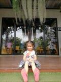 La petite fille d'enfant heureux s'asseyent sur le plancher en bois à la maison photos libres de droits