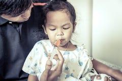 La petite fille d'enfant obtient la médecine avec une seringue dans sa bouche photographie stock libre de droits
