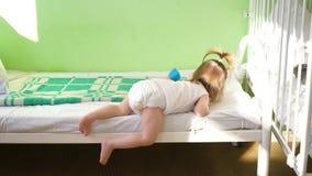 La petite fille dans la couche-culotte joue dans la salle d'hôpital près du lit avec le cube coloré mou Rétablissement d'enfant d clips vidéos