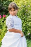 La petite fille dans la demoiselle d'honneur blanche vêtx la pose dehors Photos stock