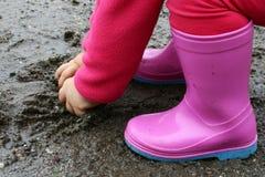 La petite fille dans des bottes en caoutchouc roses saisit la boue humide du magma Image stock